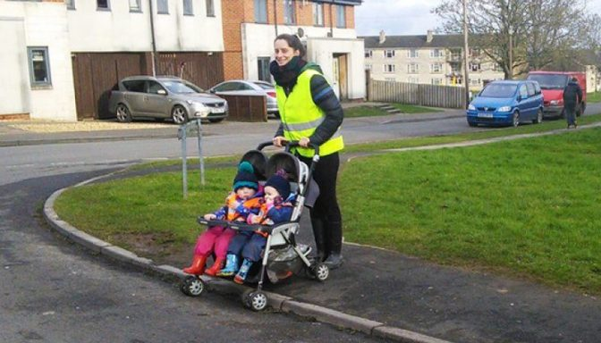 Woman crossing the road with a pushchair