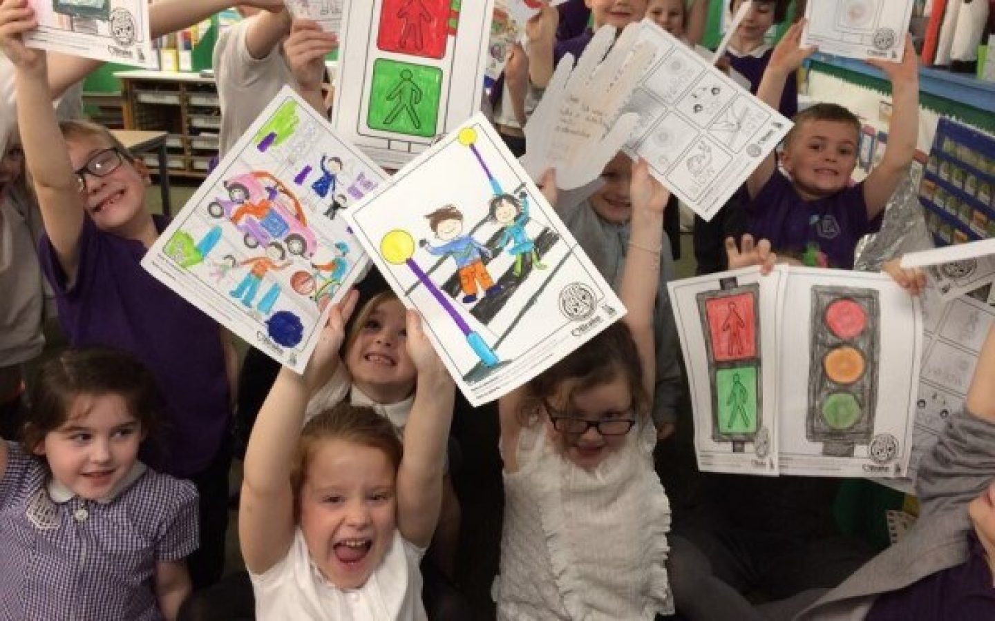 Children holding colouring sheets