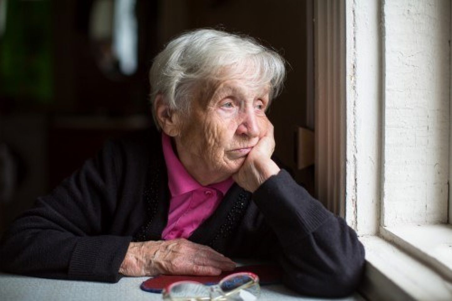 Pensive old woman looking out window