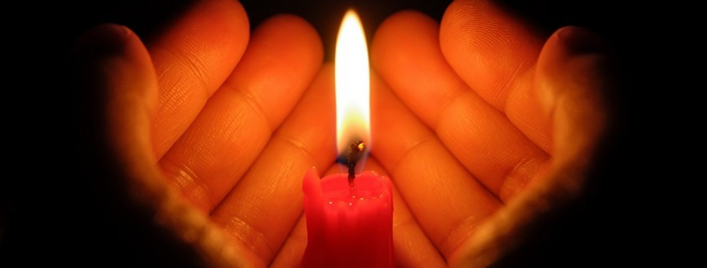 Hands around a candle