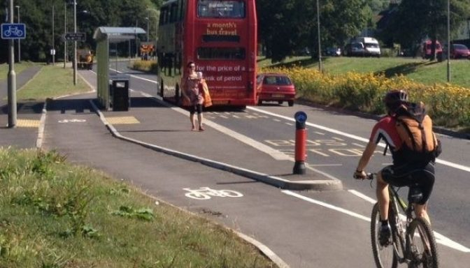 Person cycling on a cycle path that is physically separated from the road